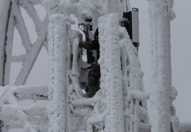 Tower climber working on ice encrusted towe