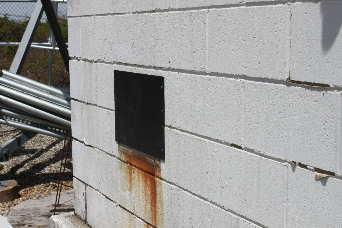 Hole in cinder block building covered with aluminum rack panel blank