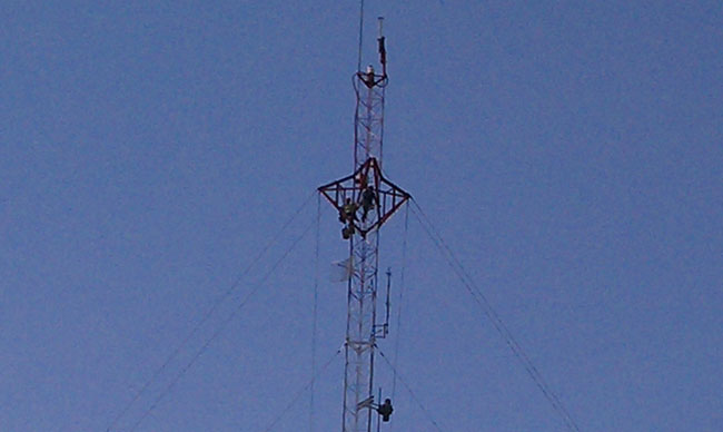 Tower workers painting torque arms on 320 foot guyed tower